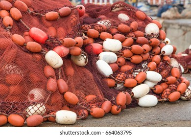 Old red fishing net with buoys on a dock in Essaouira port, Morocco