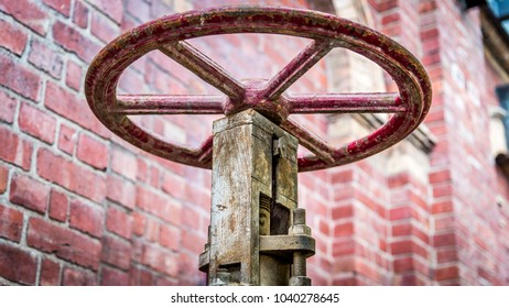 An old red Iron wheel that opens a pumphouse valve in North Melbourne, Victoria, Australia
