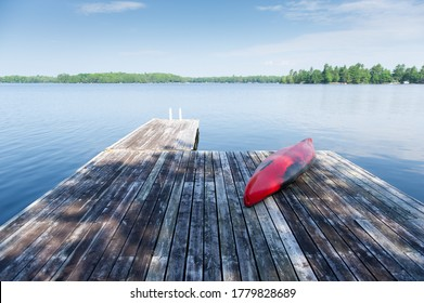 Old red kayak rest on a lake wooden pier on a summer day. Cottages are visible across the water.