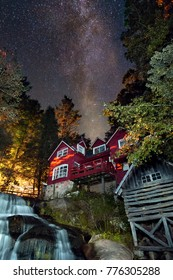 old red mill house with waterfall under stars