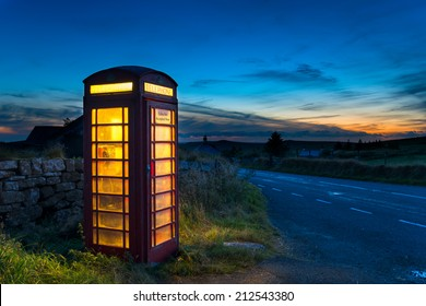 Old red phone box at dusk on a lonely country road in Dartmoor, Devon