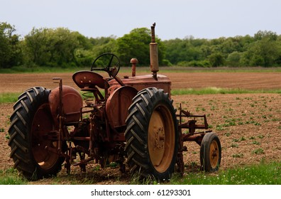 Old red rusty farm tractor at the edge of a field
