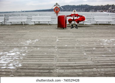 Old red santa claus on white bench and landcape of ocean