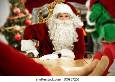 Old red Santa Claus and Santa Claus woman with elf in office