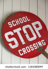 Old, red school crossing stop sign, with large white lettering and handle for crosswalk guard to hold. Isolated on white wood background.