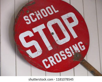 Old, red school crosswalk stop sign, with large white lettering and handle for crossing guard to hold. Isolated on white wood background.