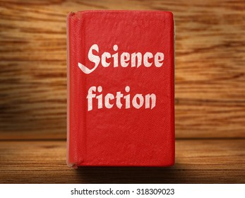 Old red science fiction book on wooden background closeup