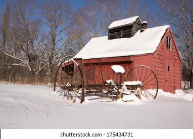 An old red sugar house on a farm in New England in the snow.
