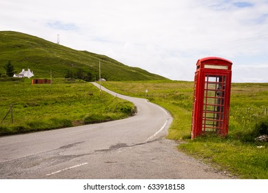 old red telephone booth next to a street, scottish highlands, Scotland