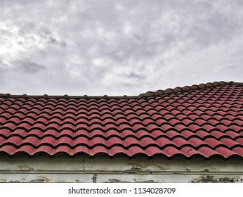 Old Red Tiled Roof Against Cloudy Sky