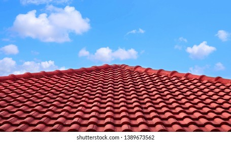 The old red tiles roof slope in pyramid shaped against white clouds and blue sky background in sunny day, architecture design concept