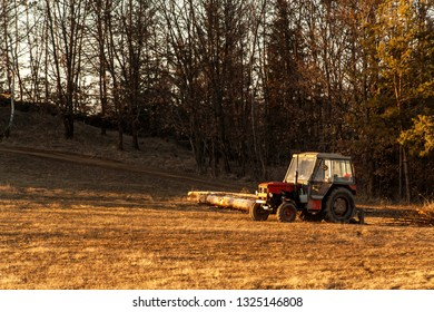 Old red tractor on the edge of a forest. Work in forest. An abandoned tractor. Landscape of the Czech countryside.