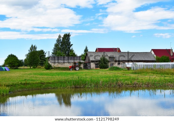 Old red tractor parked outside yard with pond, barn and green house behind in sunny summer day with cloudy sky. Colorful agriculture and countryside landscape.
