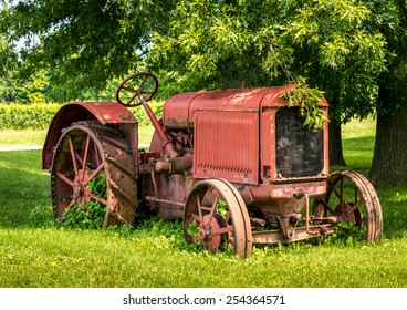 A old red tractor sits under a tree on the edge of a farm field.