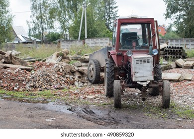 Old red tractor with trailer stands near a pile of construction