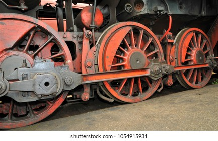 Old red train wheels of a old steam locomotive in the vintage and industrial depot of the railway