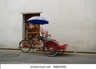 Old Red Trishaw ,three wheels vintage stop beside street in Penang town area.