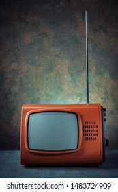 Old red tv against a dark background