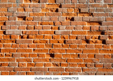 Old Red Vintage brick wall for background. Distressed Wall With Broken Bricks Texture. Retro House Facade.