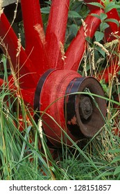 An old red wagon wheel in a field of tall grass