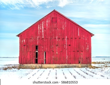 Old red weathered barn in cold snow in Midwest USA