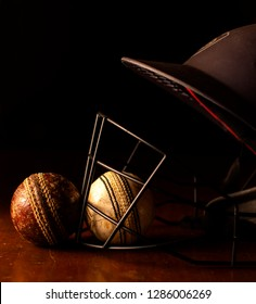Old red and white Cricket balls with a helmet on wood.