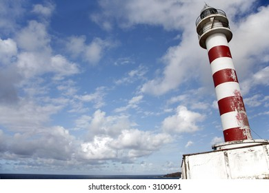 Old red and white lighthouse on clifftop with blue sky
