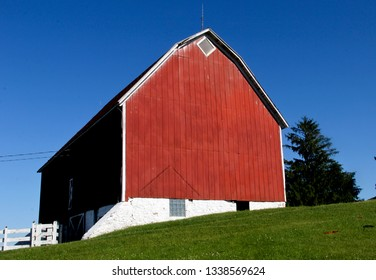 Old red wooden barn against a blue sky background