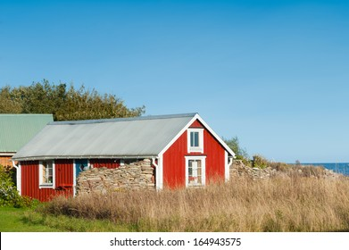 Old red wooden cottage near the beach and the fishing harbor of Blaesinge, island Oeland, Sweden.