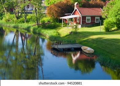 Old red wooden house in the village Hoegsby, Sweden,in the foreground the river Eman.