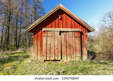Old red wooden shed with crooked doors