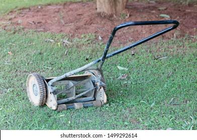 Old reel lawnmower on lush green lawn