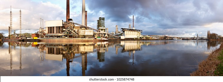 An old refinery at a canal short before sunset with clean reflection.High resolution panoramic shot of an old oil refinery at a canal.