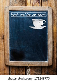 Old restaurant or coffee house menu on a rustic weathered old vintage school slate with a silhouette of a cup and the text - best coffee on earth and blank copyspace