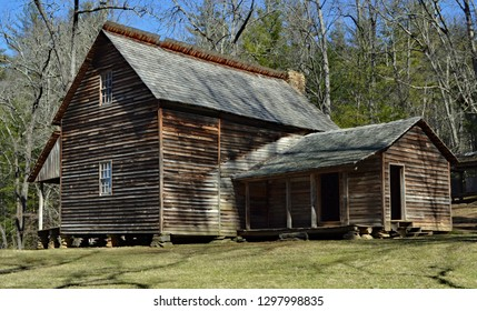 An old restored farm house sit in the woods in Appalachia during early spring.