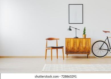 Old restored furniture in contemporary bright interior with white wall and vintage accessories, chair, lamp, wooden cupboard, rug and retro bike