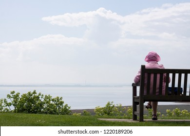 An Old Retired English woman in pink clothes sitting on the bench and enjoying seascape view.