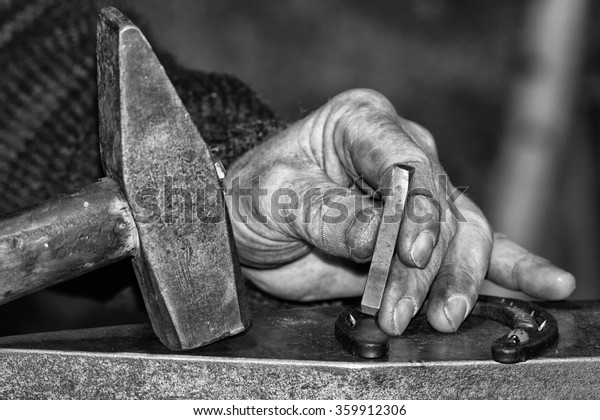 old retired man hand detail while working iron in black and white