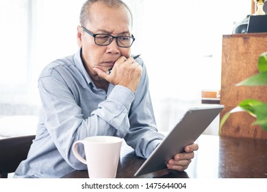 a old retired man sitting in house and looking or using tablet for working or monitoring something with drink coffee, social media or owner business concept