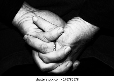 old retired woman crossed hands in black and white
