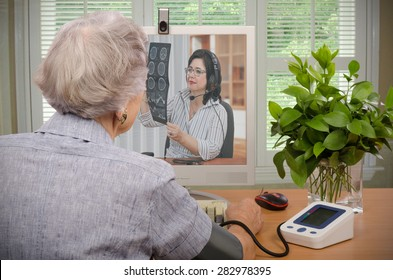Old retired woman sitting in front of monitor. She has just sent her blood pressure and pulse information to virtual doctor. At the same time, physician is looking at her CT x-ray on the screen