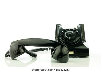 Old retro bakelite telephone with the earphone next to it. On a white background