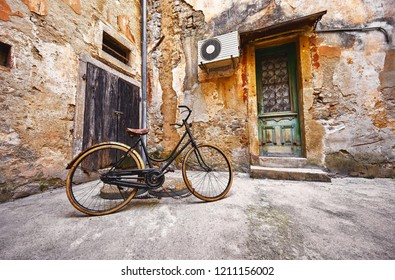 Old retro bicycle on vintage street in Croatia background aged wall and wooden door. City Lovran.