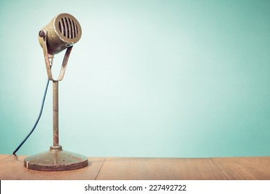 Old retro big microphone front mint green wall background