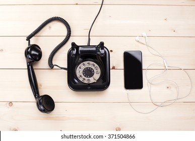 Old retro black phone and new cell phone on wooden board, top view, DOF, focus on phone