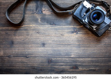 Old retro camera on vintage wooden table background