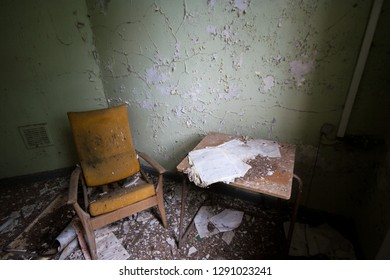 Old retro chair at an abandoned and derelict lunatic asylum/hospital (now demolished), Cane Hill, Coulsdon, Surrey, England, UK