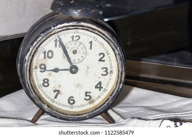 old retro clock with alarm, gray with a lot of scratches and rust