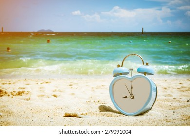 old retro clock on sand beach ,vintage color tone,abstract background to memory of last time.