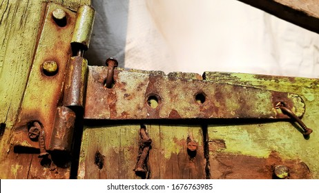 Old retro corroded metallic door hinge and nails on wooden door, damaged rusty hinge with green paint.